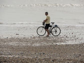 Man pushing bicycle along beach — Stock Photo