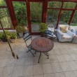 Conservatory tables chairs plants room in house next to garden — Stock Photo #27580501