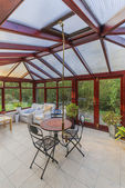Conservatory tables chairs plants room in house next to garden — Stock Photo