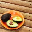 Sliced avocado on orange plate - Lizenzfreies Foto