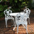White garden chairs in a backyard patio - Stock Photo