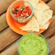 Guacamole dip with chips and salsa - Stock Photo