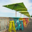 Colorful tables and chairs overlooking water — Foto Stock #19649231