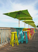 Colorful tables and chairs overlooking water — Stock Photo
