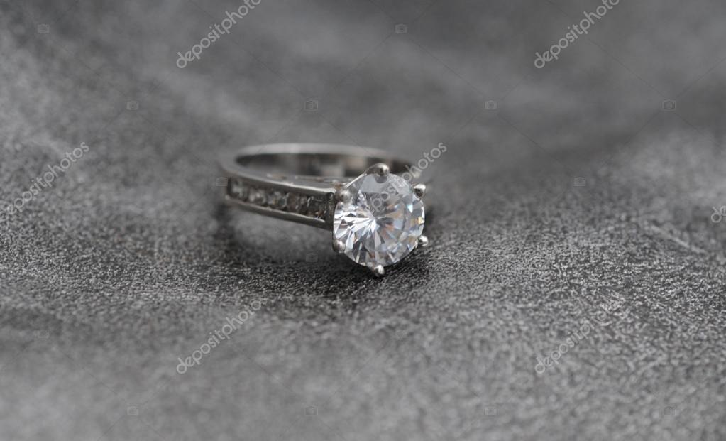 Elegant engagement ring on gray textured backgound — Photo #19661255