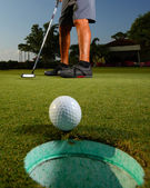 Golfer golfing and close-up of golf ball — Stock Photo