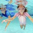 Stock Photo: Two children swimming underwater in pool