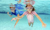 Two children swimming underwater in pool — Stockfoto