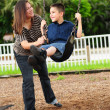 Mother and son at park on swing — Stock Photo