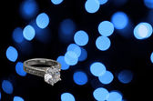 Diamond engagement ring on abstract blue background — Stock Photo