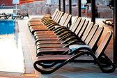 Mehrere liegestühle am pool bei sonnenaufgang. — Stockfoto