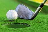 Golfbal in de buurt van het gat op de groene hof. — Stockfoto