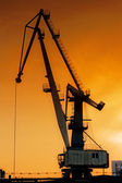Silhouette of harbor crane at sunrise. — Stock Photo