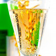 A glass of sparkling wine on the background of the bottle with a festive tinsel. — Stock Photo