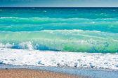 Splash van zee schuim op een zandstrand — Stockfoto