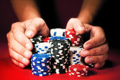 Man's hands move the winnings casino chips on red table — Stock Photo