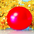 Red Christmas ball in a golden tinsel — Stock Photo