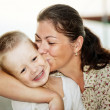 Mother kissing her child's cheek — Stock Photo