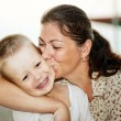 Mother kissing her child's cheek — Stock Photo #14810565