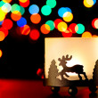 Candlestick with a figure of a deer on the background of blurred lights garlands. — Stock Photo