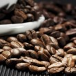 Coffee beans scattered on a black grooved — Stock Photo