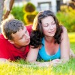 图库照片: Young couple lying on grass, and that it is considering