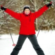 Stockfoto: Happy girl posing on skis in the winter woods.