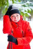 Portrait of a happy woman with ski poles in the winter woods — Stockfoto