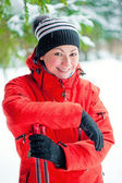 Portrait of a happy woman with ski poles in the winter woods — Photo