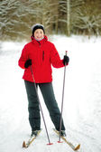 Happy girl posing on skis in the winter woods. — Stock Photo