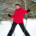 heureuse femme qui pose sur des skis dans les bois d'hiver — Photo