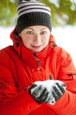 Portrait of a woman who keeps a handful of snow in her hands — Stock Photo