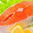 Fresh uncooked Pacific Coast Salmon with lettuce and a lemon wedge. — Stock Photo