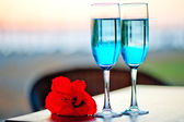 Two glasses with blue alcohol cocktail with an exotic flower on the table — Stock Photo