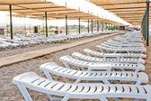Cadeiras de praia sob um dossel em uma praia arenosa — Foto Stock