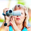 Royalty-Free Stock Photo: Woman shoots video with interest to the mini camcorder