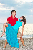 Young couple dancing on the sandy sea beach — Stock Photo