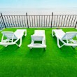 Three white beach lounger on a green deck with a view of the sea. - Stock Photo