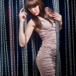 Girl with bangs in a beige dress posing curtains of strass — Foto Stock