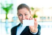 Een lachende meisje in klederdracht toont een blanco visitekaartje — Stockfoto
