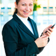 Stock Photo: Young happy business womwith mobile phone in hand
