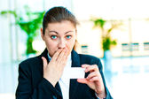 Dark-haired businesswoman with surprise looks at the business card — Stock Photo