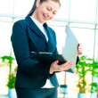 Young happy business woman with an open folder in hand — Stock Photo