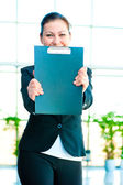 Smiling girl shows the empty office folder — Stock Photo