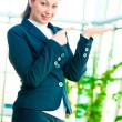 Girl in a business suit holding something on the palm and finger pointing to it  — Stock Photo