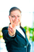 Girl in a business suit showing gesture - victory hand — Stock Photo