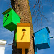 Three colorful birdhouse attached to a tree against the sky - Stock Photo
