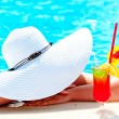 Girl in a wide white hat resting in the pool — Stock Photo