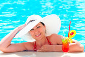 Girl in a white hat relaxes in the pool — Stock Photo