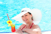 Happy young girl with cocktail relaxing by the pool — Stock Photo